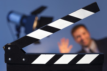 Equipment for shooting and create a video blog. clapperboard and flashlight with TV presenter in a suit or model. Man waving at the camera