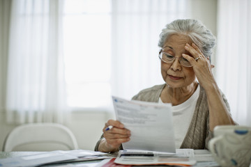 Anxious elderly woman is worried about how she can pay the bill she has received.