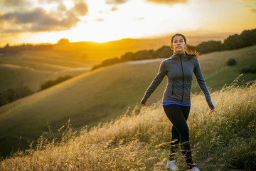 Young woman enjoys a walk through the countryside at sunset.