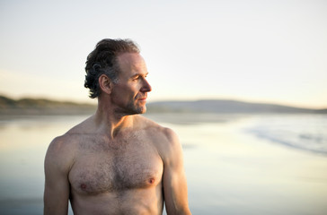 Shirtless man looking into distance on the beach.