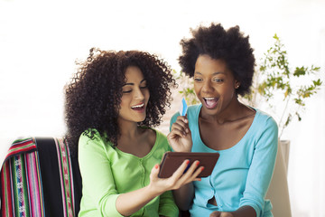 African american friends with mobile phone and credit card.