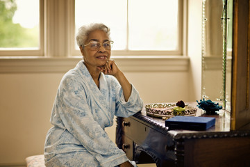 Senior woman wearing a bathrobe smiles slightly as she sits at a dressing table and poses for a portrait.
