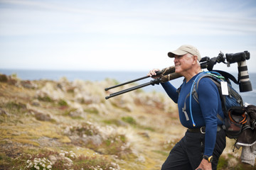 Photographer carrying his equipment along the coastline.