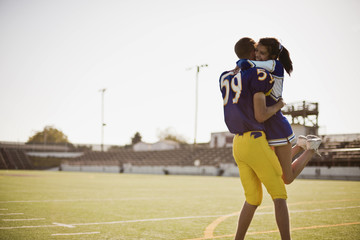 Football player picking up cheerleader in a lover's embrace.