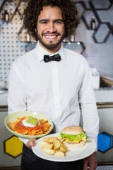 Waiter holding plates of snacks and burger in bar