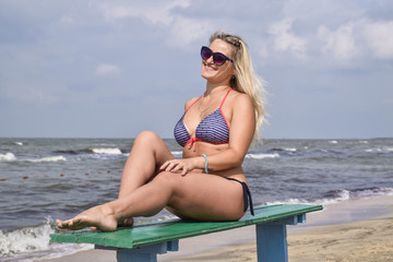 Beautiful blond woman sitting on a bench by the sea