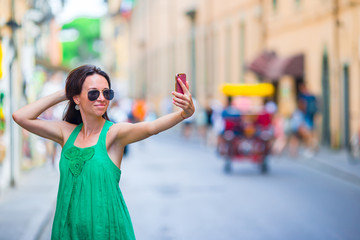 Woman take selfie by her smartphone in city. Young attractive tourist taking self photo outdoors in italian city