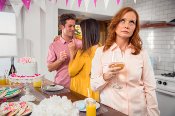 Mature older person at a party family event feeling left out fifth wheel jealous envious