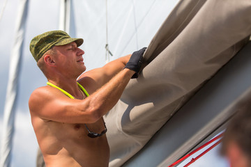Fototapete - Man skipper sets sails on sailing boat.