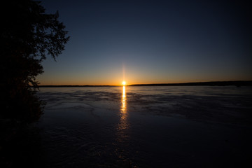 Sunset over a frozen lake in winter
