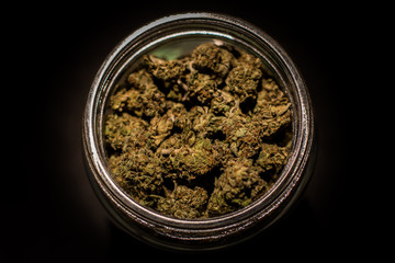 Marijuana or cannabis jars of dried flower bud isolated black background
