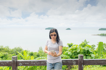 asian woman selfie with seascape against blue sky