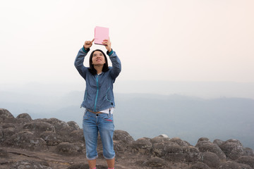 young woman selfie during Sunset on mountain with landscape view