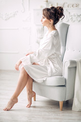 Young beautiful bride in elegant white robe sitting on a chair in a bright interior and looks out the window