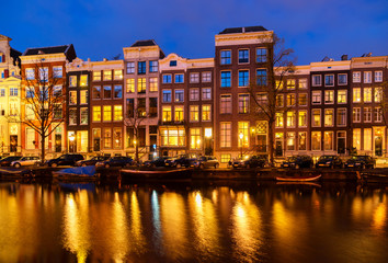 Typical dutch houses over canal with reflections illuminated at night, Amsterdam, Netherlands