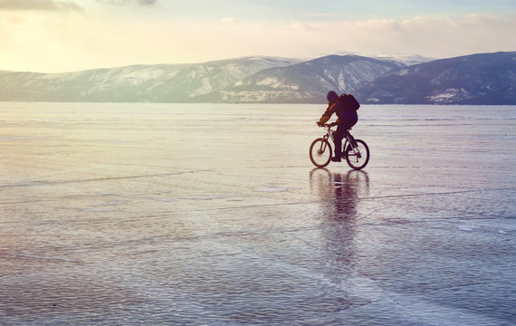 Lonely biker with backpacks on bike on ice of Lake Baikal. Against the background of sunset sky, ice surface. Winter sport concept. Cycling.