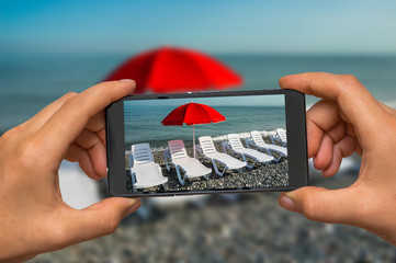 Taking photo of sunbathing beds and red umbrella with phone