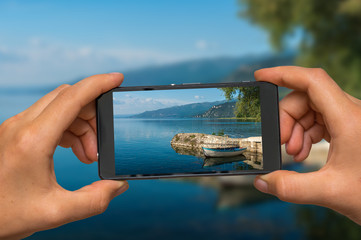 Taking photo of Ohrid lake in Macedonia with mobile phone