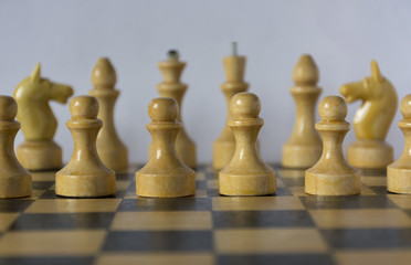 wooden white chessmen, chess pieces stand on a chessboard in the