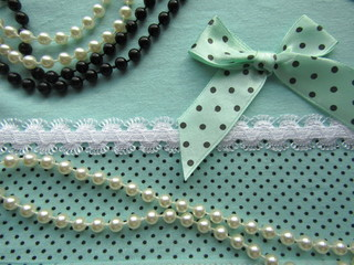 Texture of green fabric with polka dots with white lace large with a bow and beads