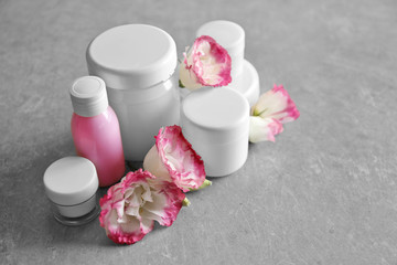 Cosmetic bottles and eustoma flowers on light wooden background