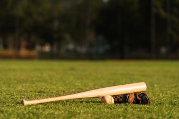 Baseball bat ball and glove on grass field