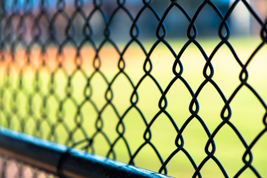 View through chain link fence from inside dugout with baseball field blurred in background