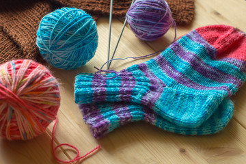 Handmade knitted baby multicolored socks and skeins