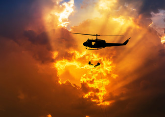 silhouette soldiers in action rappelling climb down from helicopter with military mission counter terrorism assault training on sunset background
