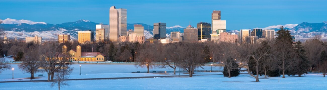 Denver skyline at sunrise in winter with snowy foreground and snow-capped Rocky Mountains in background