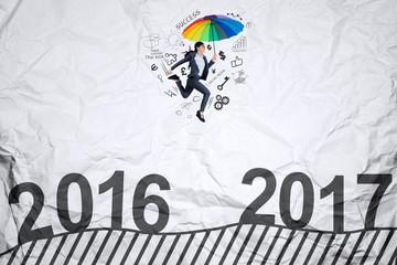 Woman with umbrella jumps toward 2017