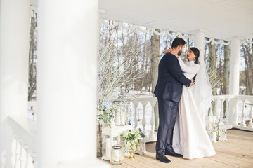 Bride looks in groom's eyes holding his neck in her tender hands