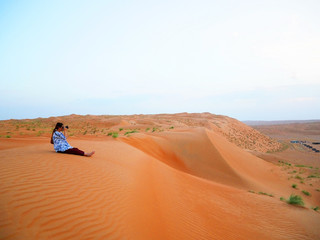 Girl taking photo in the Wahiba desert, Oman