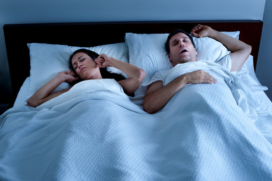 Snoring man sleeping snoring from obstructive sleep apnea in bed at night with tortured wife plugging ears with fingers