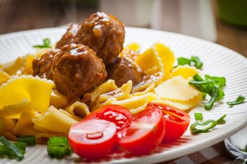 Tagliatelle, meatballs in dark sauce and tomato.