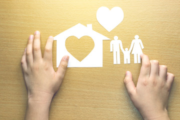 children hands with small model of house and heart and family on