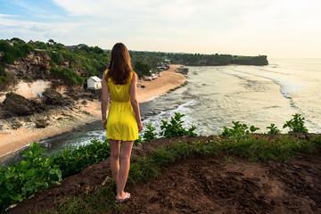 Girl in yellow dress looking forward from the cliff  on Balangan beach. Bali. Indonesia.