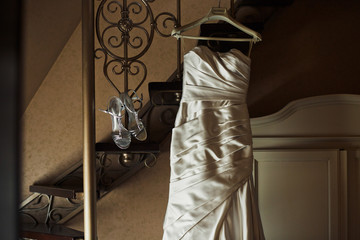 The wedding shoes and dress hang on the stairs