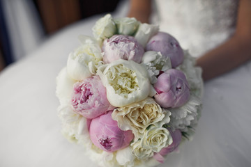 bride holds colored bouquet of peonies