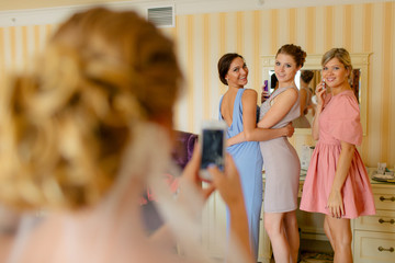 Beautiful bridesmaids in the colorful dresses are taking a photo