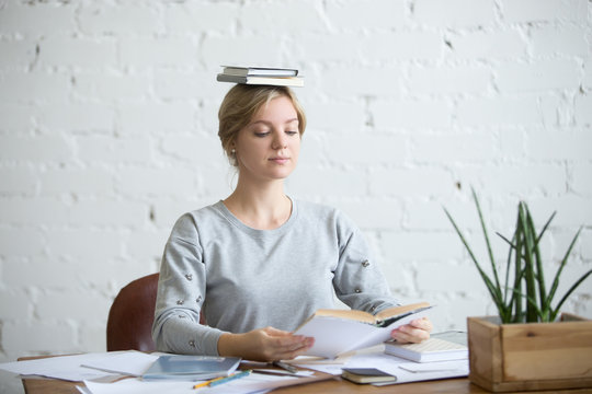 Portrait of a young attractive woman at the desk with books on her head, sitting straight, reading a book. Education concept photo, lifestyle