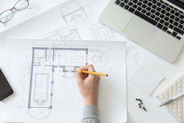Top view of a hand making an architect drawing at the working desk, close up, education concept photo