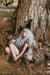 Chica joven con el pelo blanco y aspecto mágico apoyada sobre un árbol en otoño