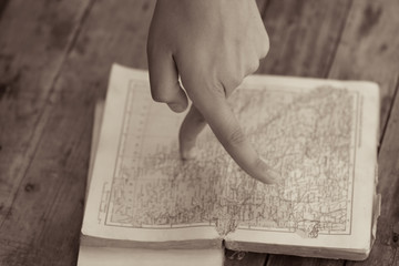 Fingers marching on the map in an old book