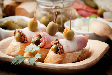 Tapas with sliced bacon, olives and cucumber on a wooden table.