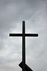 Black metal cross under a cloudy sky