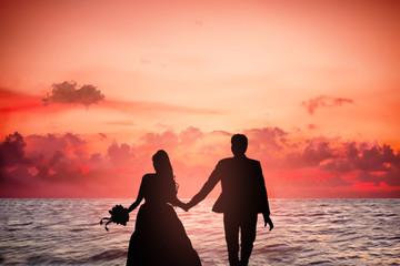 giovane coppia di sposi in spiaggia al tramonto