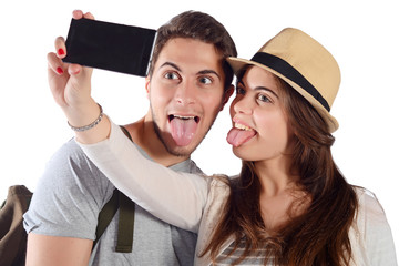 Young beautiful couple on a trip and taking selfie.