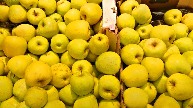 Appetizing fruit fresh yellow apples on the counter in the store