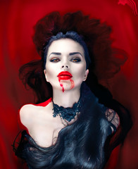 Halloween. Sexy vampire woman lying in a bath full of blood
